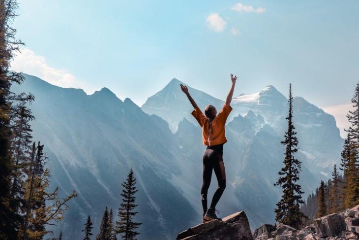 Une femme au sommet d'une montagne les bras levés au ciel
