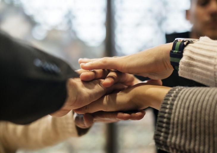 Des personnes réalisant un high five groupé