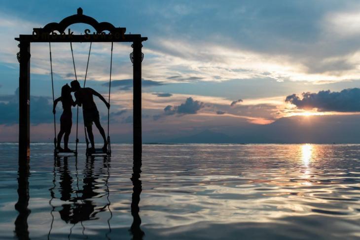 Un couple sur une balançoire au milieu de l'eau