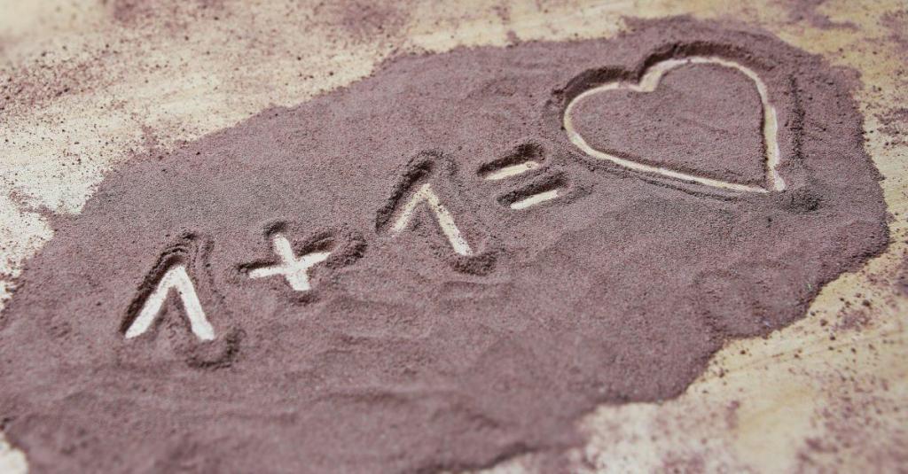 1+1 écrit sur le sable avec un coeur