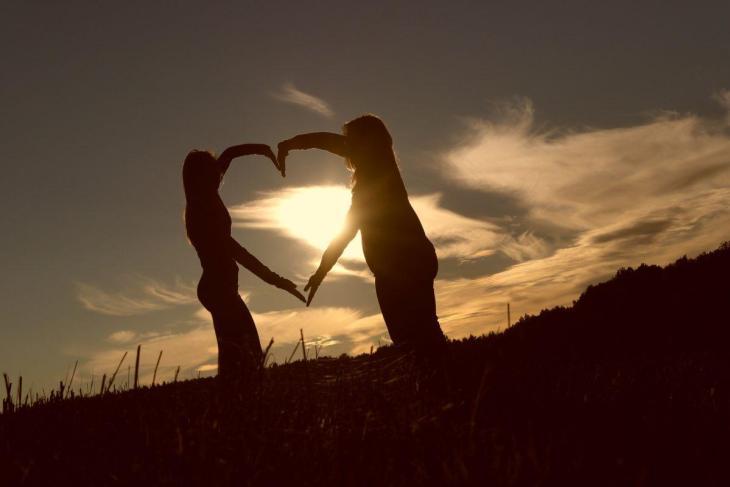 Deux enfants faisant un coeur avec les bras