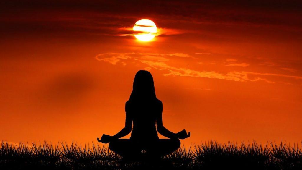 Une femme en éveil spirituel au couché du soleil