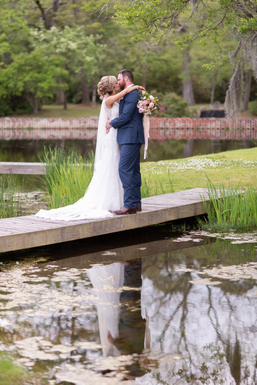 Bride and groom reflecting in the pond by the statue - Brookgreen Gardens