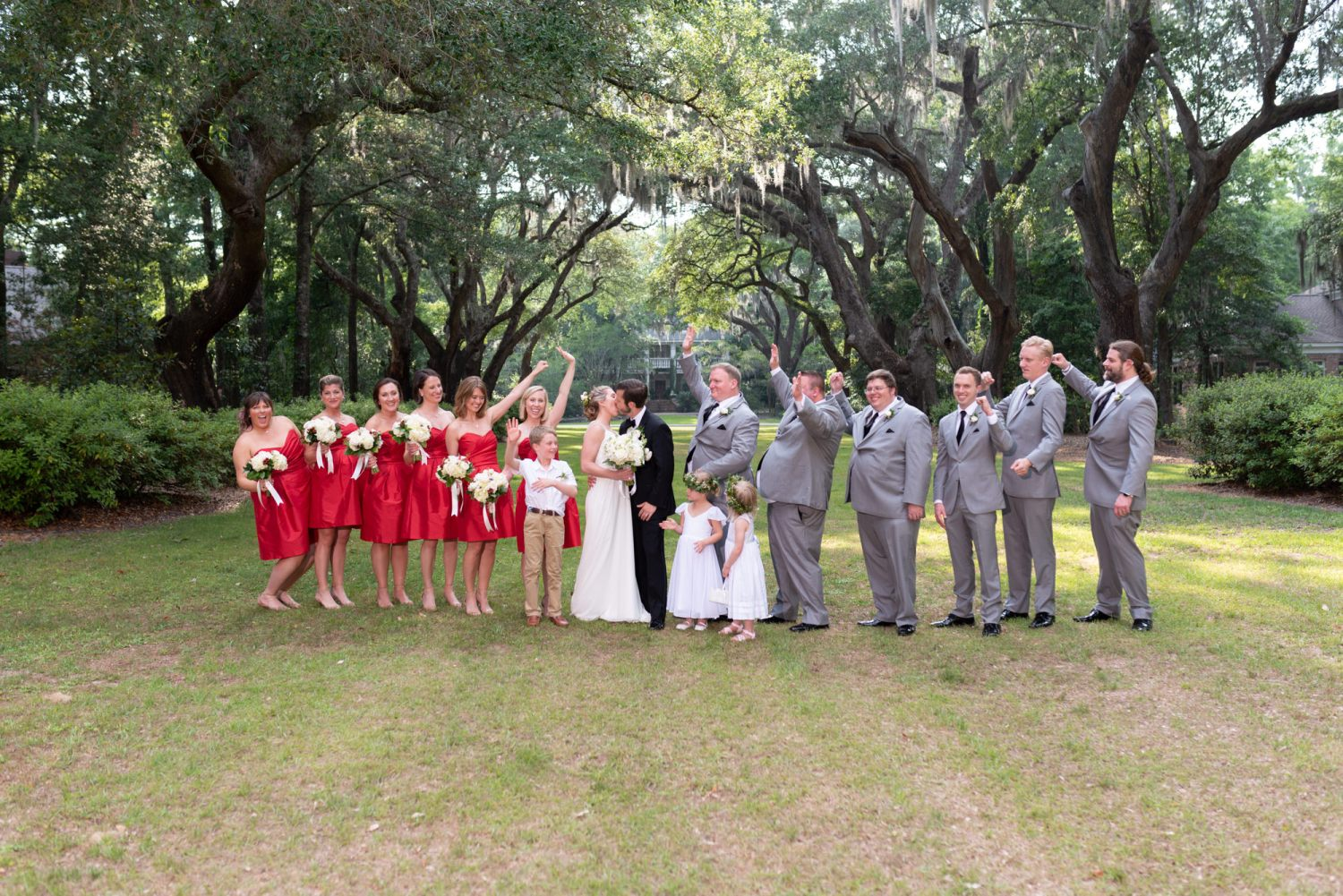 Bride and groom kissing with wedding party cheering - Wachesaw Plantation