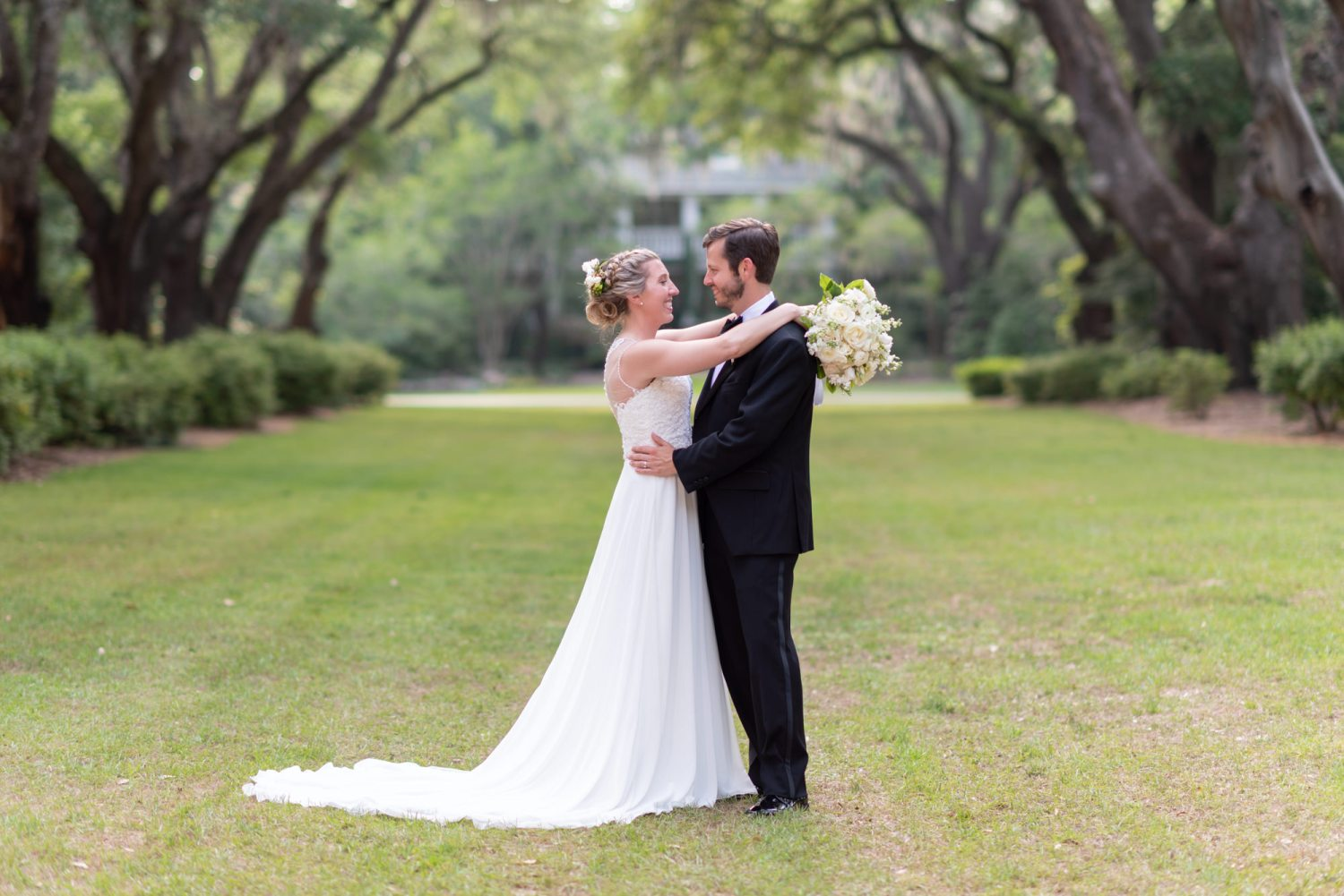 Bride putting her arms around the groom - Wachesaw Plantation