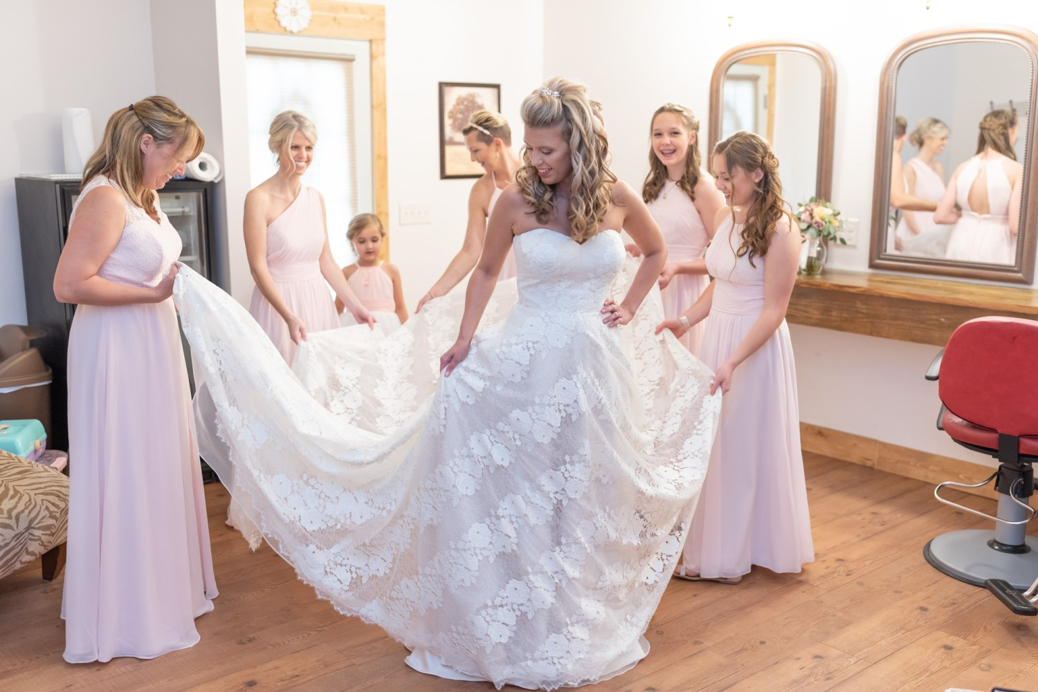 Bridesmaids helping with the brides dress - Wildhorse at Parker Farms