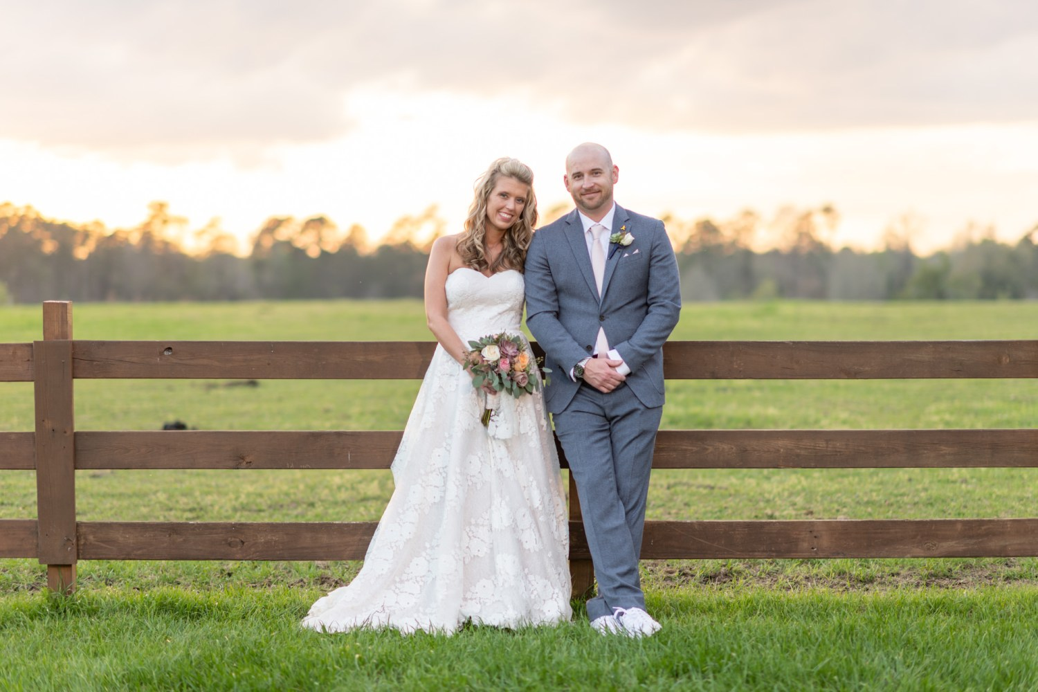Casual portrait of the bride and groom leaning against the fence  - Wildhorse at Parker Farms