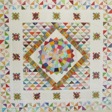 Scrappy round-robin medallion quilt with half-square triangles, granny squares and a Dresden plate