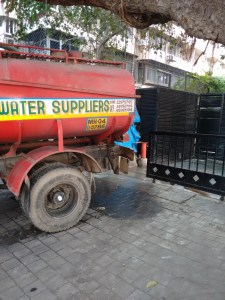 water tanker backs up to a gate from a road