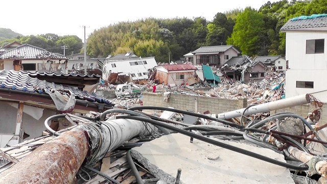 Photo showing destroyed village - lots of debris, cables and collapsed houses