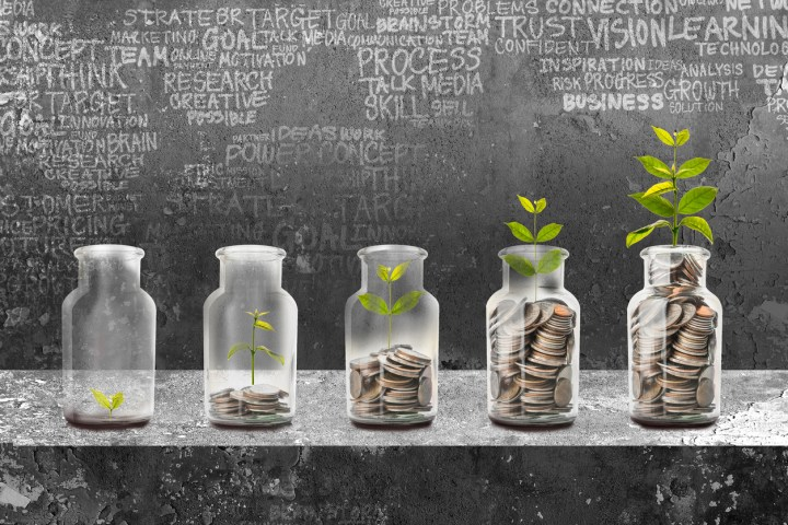Concept image showing a row of glass bottles with increasing amounts of coins in them, and a bigger plant growing out of each