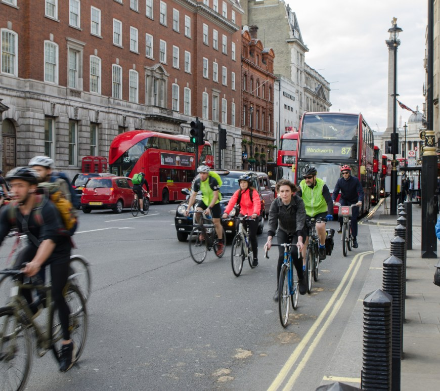 Front view of Cyclists, cars and buses riding on london street
