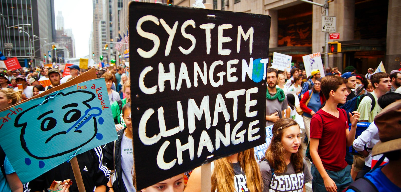 """Climate march with people holding a sign saying """"System Change Not Climate Change"""""""