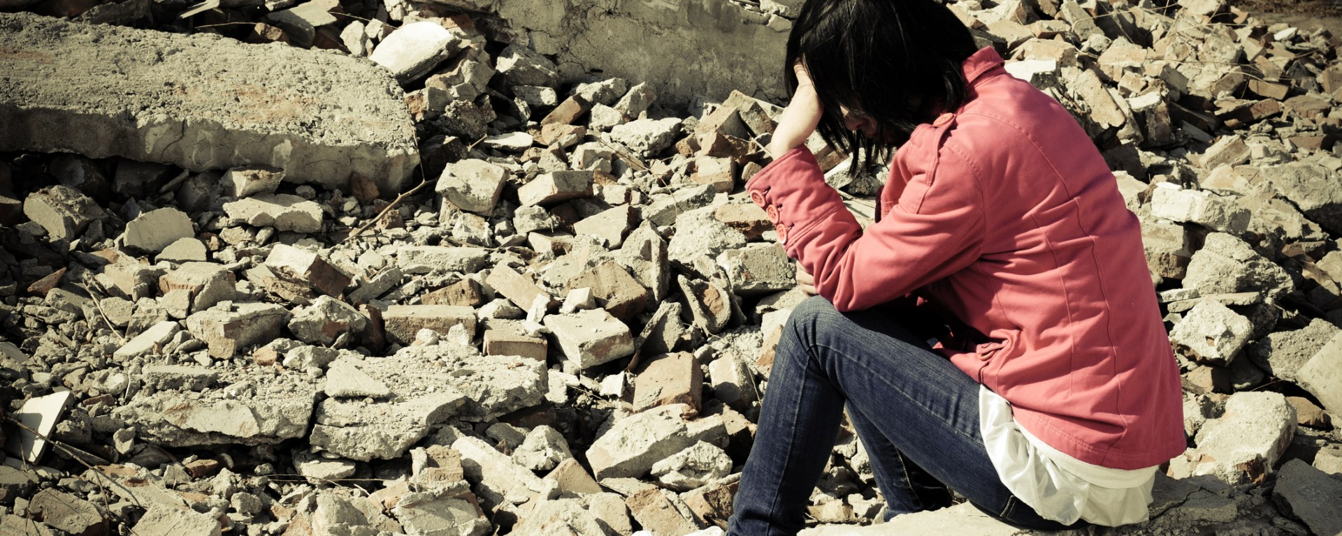 A woman sitting on a brick next to a pile of rubble