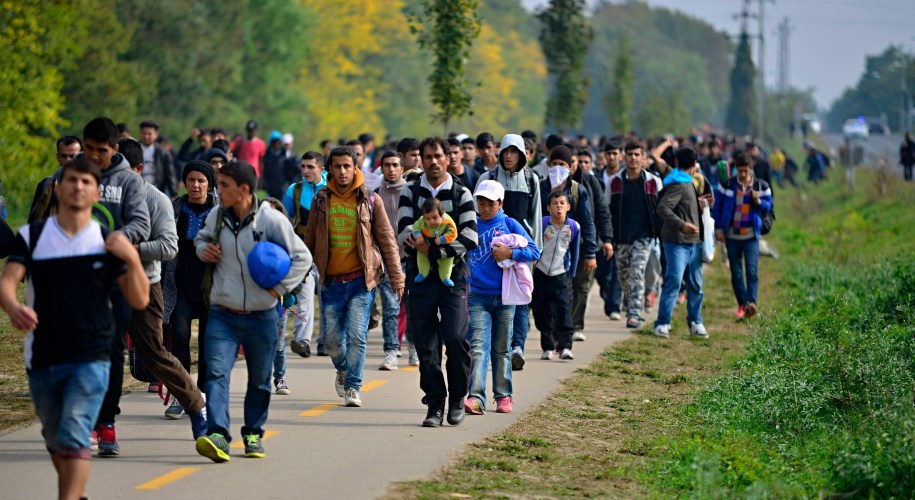 A group of refugees leaving Hungary, walking down the road carrying their things