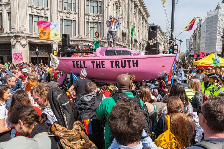"Extinction Rebellion protesters in London, aboard a big pink boat with the words ""Tell the Truth"""