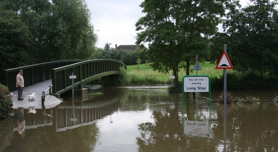 A man and his dog stand at the end of a footbridge over a flooded car park. Sign reads 'Long Stay'.