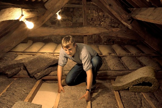 Worker installing roof-insulation material from sheep's wool