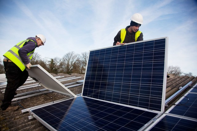 Two men install solar panels on a barn roof on Grange farm, near Balcombe.