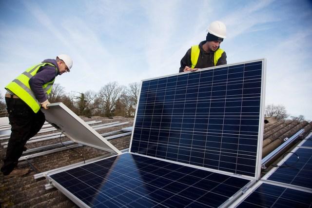 Two men install solar panels on a barn roof on Grange farm, near Balcombe.