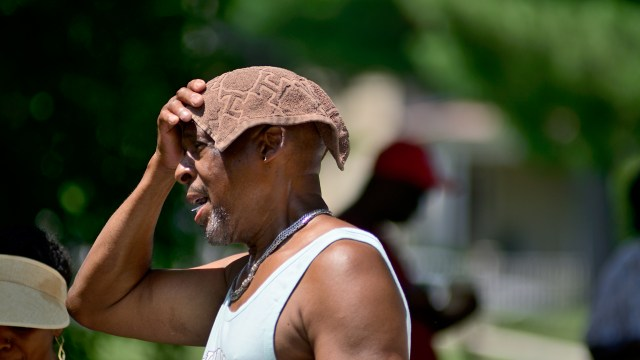 Man covering his head with a small towel to protect it from the sun.