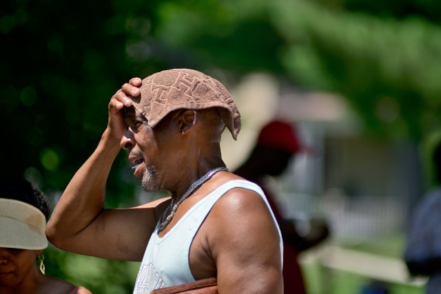 African-American man covering his head with a small towel to protect himself from excessive heat.