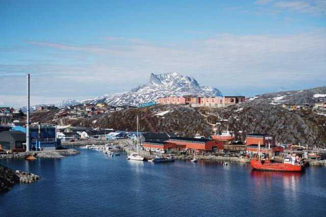 Photo of a port in Nuuk Greenland. there is a snow capped mountain in the background and boats in the harbour.