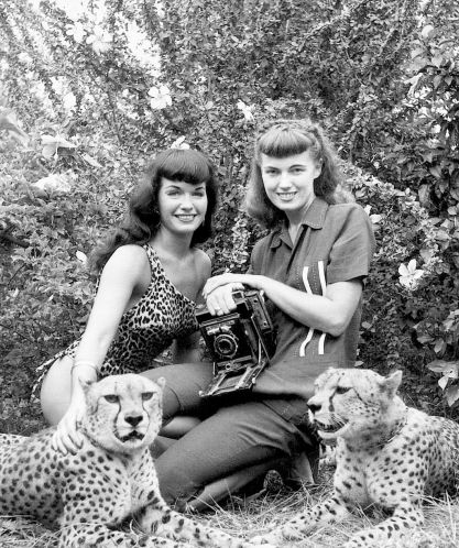 Bunny Yeager and Bettie Page flanked by cheetahs