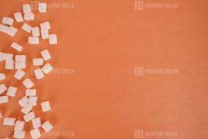 Cube sugar on orange background stock photo