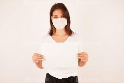 Girl in medical mask holding sign