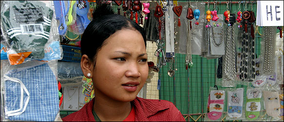 Srey Rath at her trinket and jewelry kiosk in Cambodia, after recovering from her ordeal.
