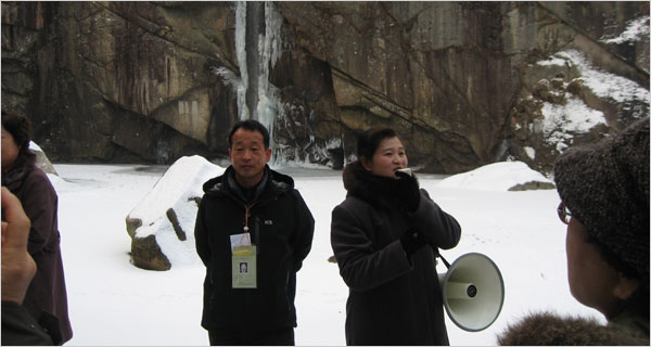 A South Korean tourist, left, and a North Korean guide at Pakyon Falls, the first stop on a tour.