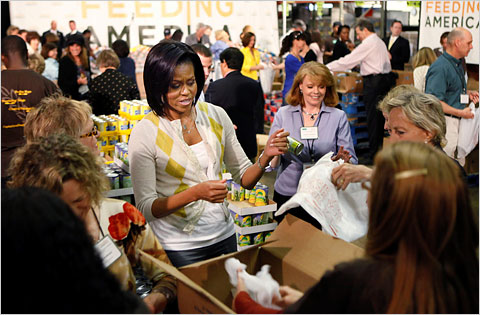 Michelle Obama and lawmakers' spouses pack bags of food for needy families.