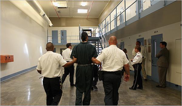 Guards escort a prisoner inside the privately run Saguaro Correctional Center in Eloy, Ariz