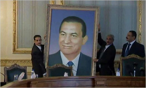 A portrait of former President Hosni Mubarak was removed from a wall in the main cabinet building in Cairo on Sunday.