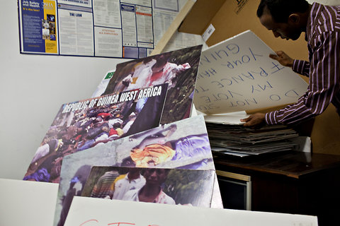 Mamadou Maladho Diallo, a community organizer and journalist, goes through signs used for recurring demonstrations for human rights in Guinea, at the Pottal Fii Bhantal Fouta Djallon office.