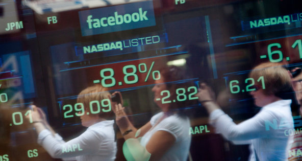 Pedestrians reflected in a window near a display of the share price for Facebook in May.