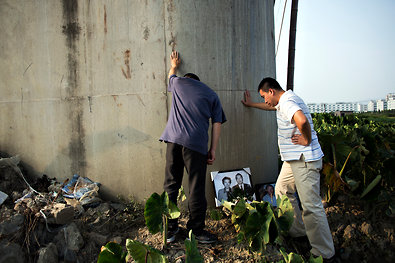 Henry Cao, left, and his brother, Leo, at the site of a train crash that killed their parents and injured Henry in Wenzhou last year.