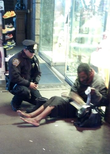 NYPD officer Lawrence DePrimo gives shoes to Jeffrey Hillman, who is homeless and barefoot