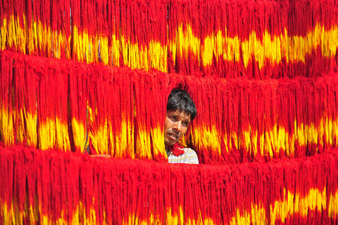 An artisan hanging freshly dyed strands of multicolored thread used in Hindu rituals, at Lalgopalganj, a town in Allahabad district of Uttar Pradesh.