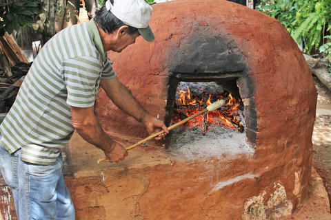 Roasting a chipa caburé, a type of cake, in a tatakua, or traditional oven.