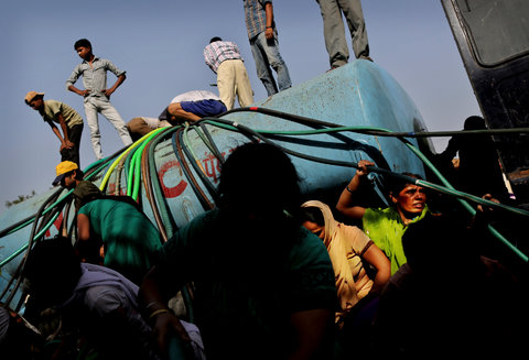 People gathered around a water tanker to collect drinking water at a slum in New Delhi on May 23.