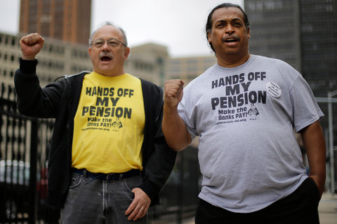 Two retired Detroit workers, William Davis, right, and Mike Shane, left, protested cuts in July.