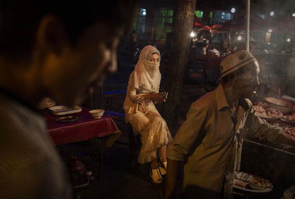 8月,新疆喀什一名戴头巾的女性在市场的小吃摊前。