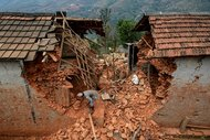 A resident of the village of Sindhupalchowk in Nepal tries to clear debris following Saturday's earthquake.