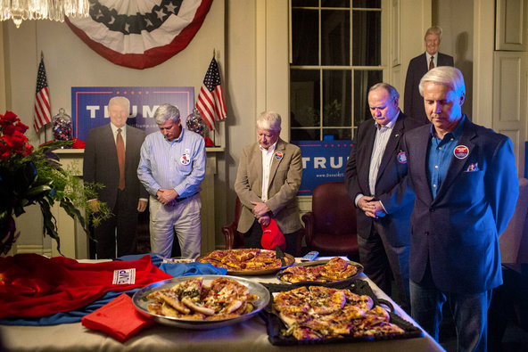 Mark Jennings, left, Tommy Shaw, Chuck Sanders and Perry Hooper prayed before eating pizza on Tuesday at a returns watch party in Montgomery, Ala.