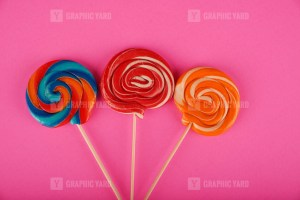 Assorted round lollipops on pink background