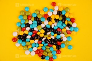 Colorful candy isolated on yellow background stock photo