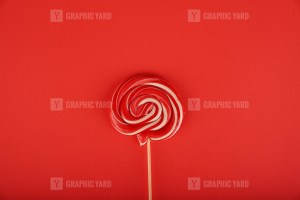 Delicious swirl lollipop isolated on red background