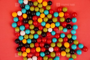 Multicolored round dragee candies on red background